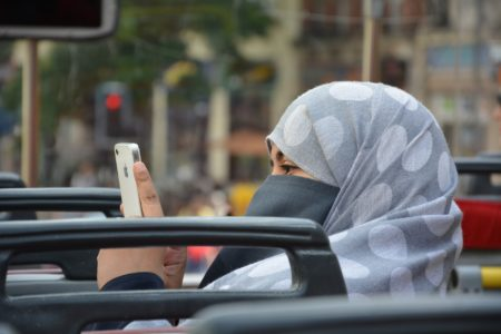 A Muslim lady with a headcovering and a smartphone