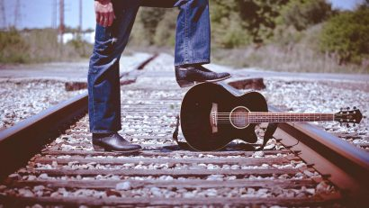 I Feel Like Traveling On -- a man with a guitar on a railroad track