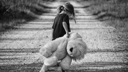 A little girl holding a teddy bear